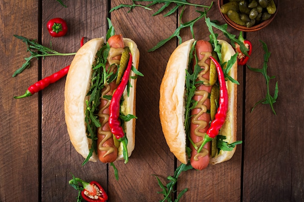 Hot dog with pickles, capers and arugula on wooden table.