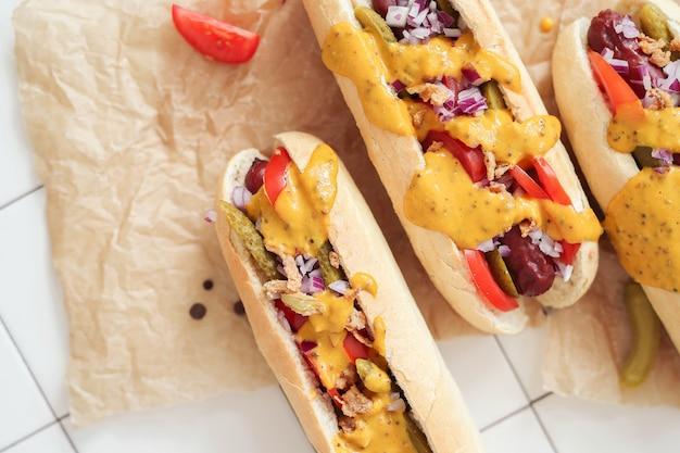 Hot dog con salsa sulla superficie bianca
