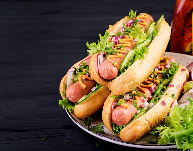 Hot dog with sausage, cucumber, radish and lettuce