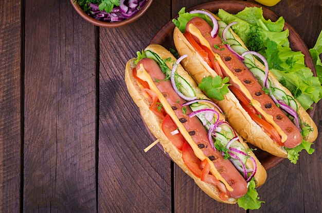 Хот-дог с колбасой, огурцом, помидорами и листьями салата на темный деревянный стол. летний хот-дог. вид сверху
