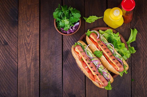 Hot dog with  sausage, cucumber, tomato and lettuce on dark wooden table. summer hotdog. top view