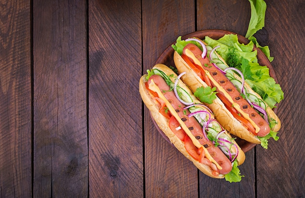 Hot dog with  sausage, cucumber, tomato and lettuce on wooden background