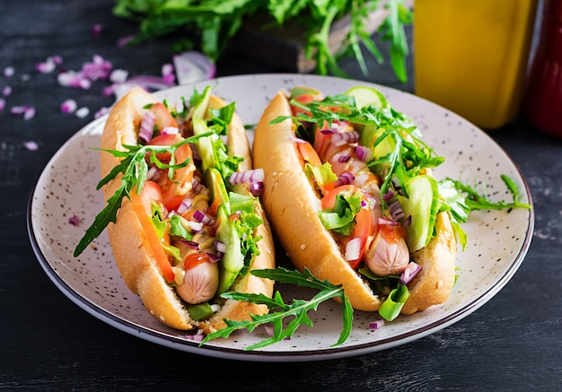 Hot dog with sausage, cucumber, tomato and red onion on dark table.