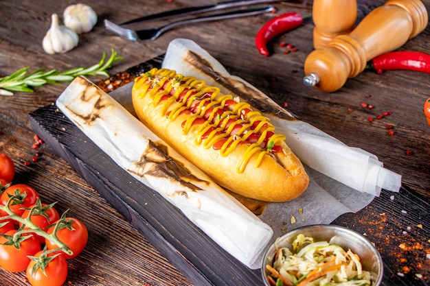 Hot dog with sausage is located on a wooden board