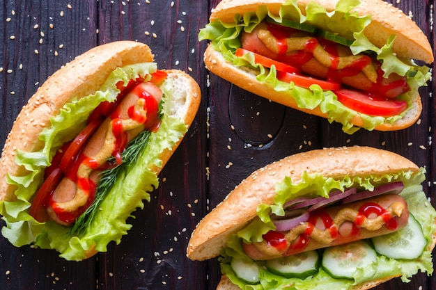 Hot dogs of different tastes on a black background with sesame seeds