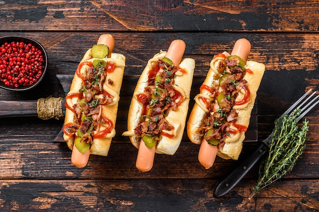 Hot dogs fully loaded with fried bacon, onion and pickled cucumbers. dark wooden background. top view.