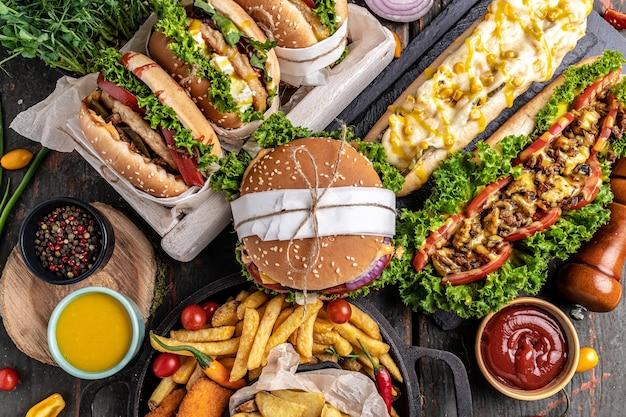 ホットドッグ、ハンバーガー、フライドポテトを木製のテーブルに。ファーストフードスナック。上面図。