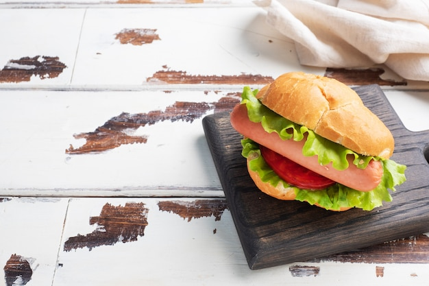 Хот-доги на деревянной доске. хот-дог с листьями салата помидор и колбаса. копировать пространство
