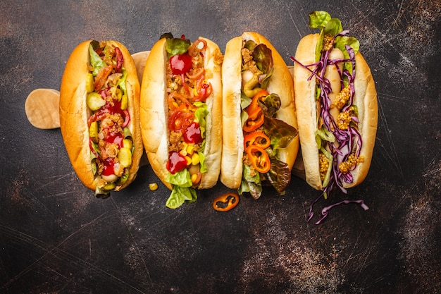Hot dogs with assorted toppings on a dark background, top view, copy space.