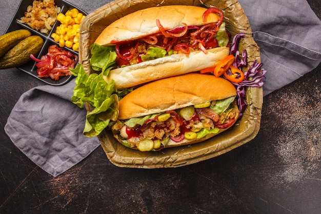 Hot dogs with assorted toppings on a dark background, top view.