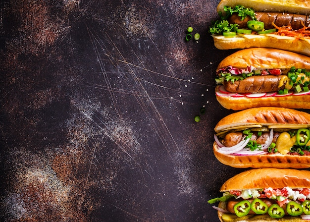 Hot dogs with different toppings on dark background, copy space, top view,