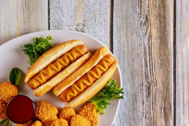 Хот-доги с горчицей и куриными наггетсами с соусом. американский фаст фуд.