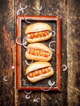 나무 테이블에 겨자와 토마토 소스 핫도그.