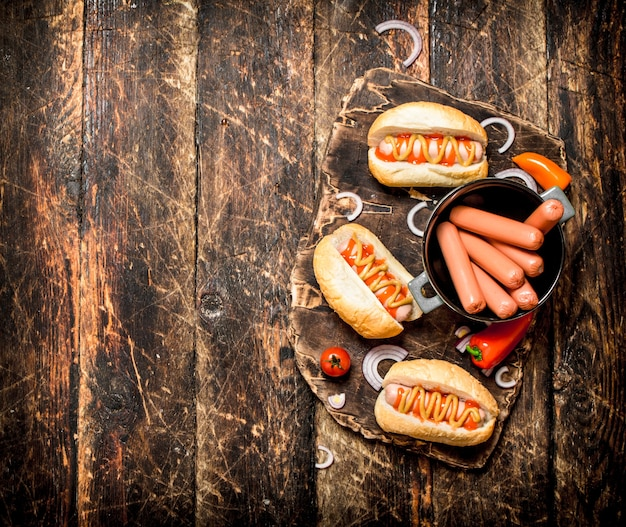 Hot dogs with mustard, onions and tomatoes on wooden table.