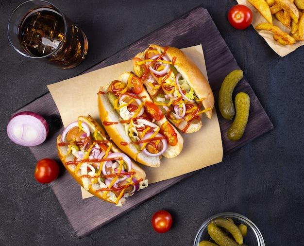 Хот-доги с овощами, горчицей и кетчупом на разделочной доске на темном фоне, вид сверху
