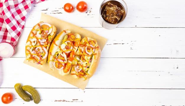 Хот-доги с овощами, горчицей и кетчупом на разделочной доске на белом деревянном столе, вид сверху, copyspace