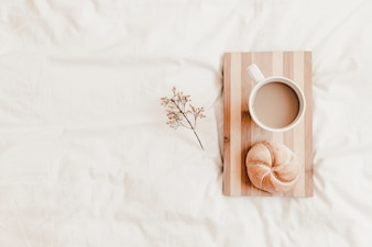 Hot drink and bun on cutting board on white bedsheet