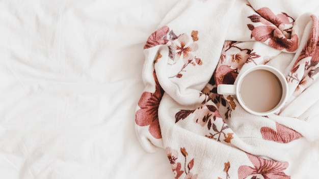 Hot drink in beautiful patterned plaid on bedsheet