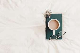 Hot drink, eyeglasses and herb lying on book on bedsheet