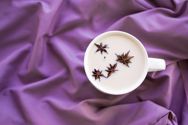 秋冬コンセプトのホットドリンク。紫色の布の背景に白いカップのスターアニススパイスフルーツとホットミルク