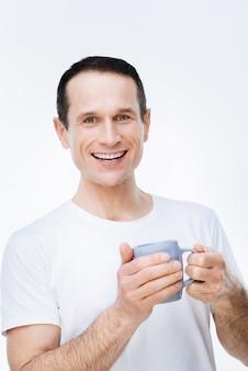 ホットドリンク。笑顔で休憩しながらお茶を楽しんで幸せなポジティブなナイスマン