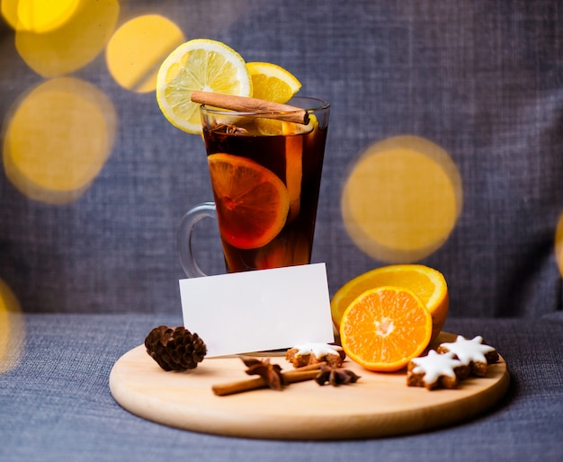 Hot drink, mulled wine red in a cup of glass on a wooden background