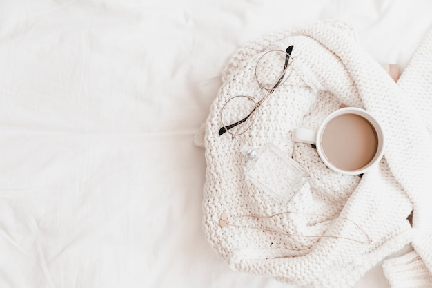 Hot drink, necklace, eyeglasses and perfume on sweater placed on bedsheet