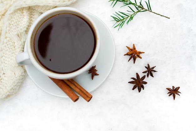 Горячий напиток на холодном снегу булочки с корицей и зерновой анис