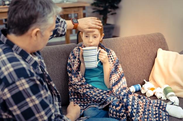 温かい飲み物。病気に苦しんでいる間彼女のお茶を持っている悲しい元気のない女の子