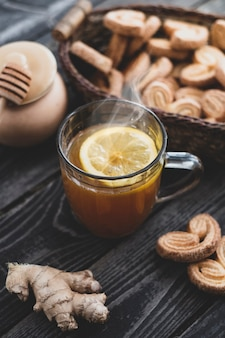 Hot drink tea with lemon, honey and ginger with gingerbread cookies on wooden background