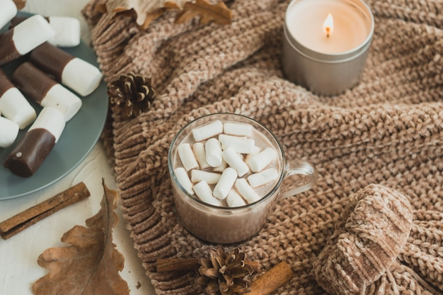 Hot drink in winter or autumn with cocoa, chocolate and marshmallows in a cup with a knitted warm sweater and scented candles, top view.