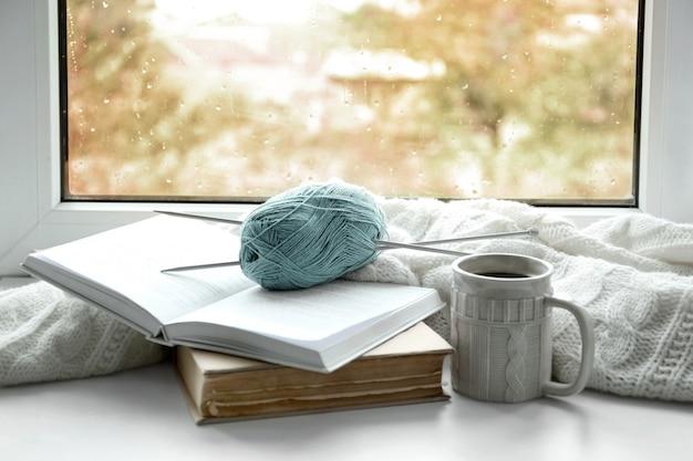 本、糸、窓辺に格子縞のホットドリンク