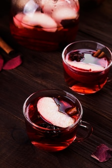 Hot drink with hibiscus red tea with apple, cinnamon and anise in glass teapot and two glasses