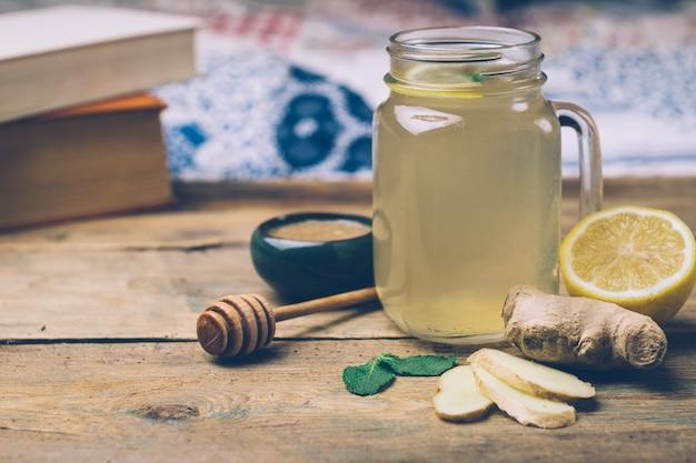 蜂蜜、レモン、木製の背景に生ingerのホットドリンク