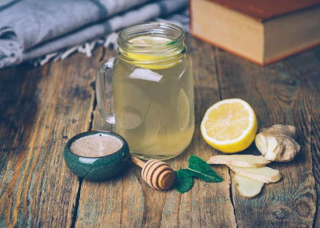 Hot drink with honey, lemon and ginger on wooden background