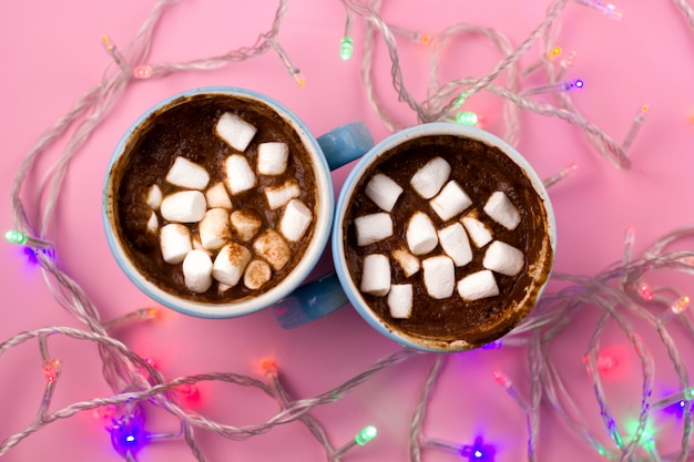 Hot drink with marshamllows in blue cups top view and shiny electric garland lights
