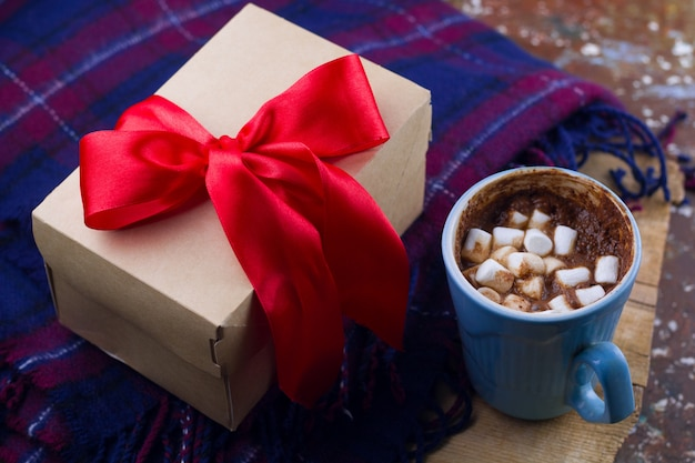 Hot drink with marshmallows,plaid  and gift box with red satin ribbon top view cozy holiday