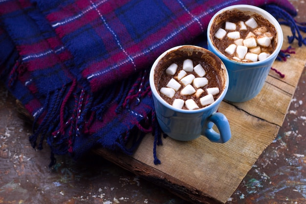 Hot drink with marshmallows plaid  top view cozy home