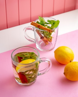 テーブルの上のスパイシーなペッパーミントシナモンレモンとホットドリンク