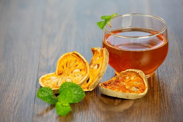 Tè caldo secco alla frutta bael in una tazza di erbe tailandesi