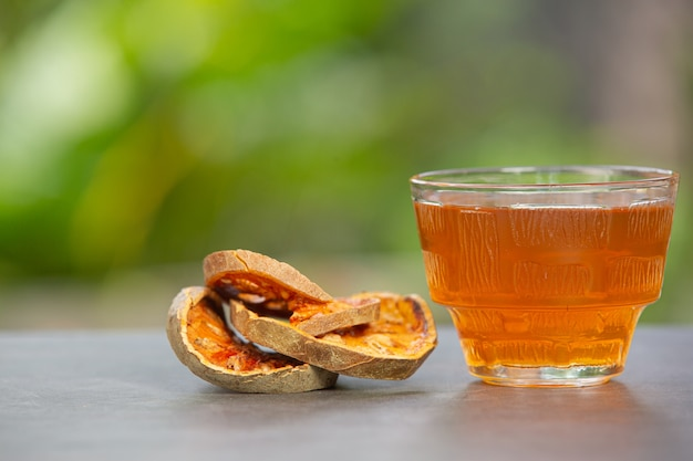 Hot dry bael fruit tea in a thai herbal cup