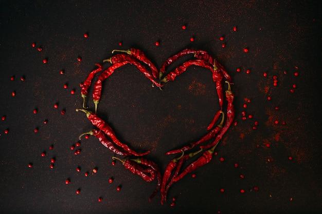 Hot dry red pepper over black background. chilli pepper heart.
