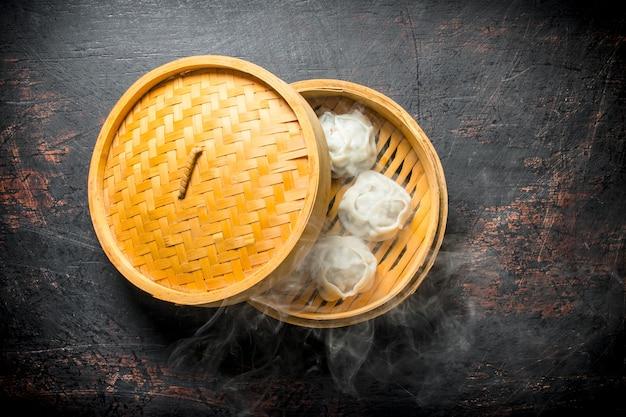 Hot dumplings manta in a bamboo steamer on dark rustic table.