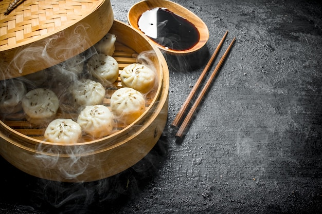 Hot dumplings manta in a bamboo steamer with soy sauce.