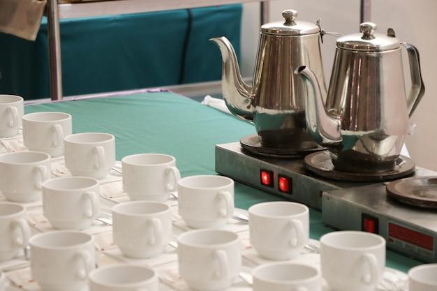 아침 하루에 hotal 테이블에 녹색 직물에 컵이 달린 뜨거운 전기 주전자