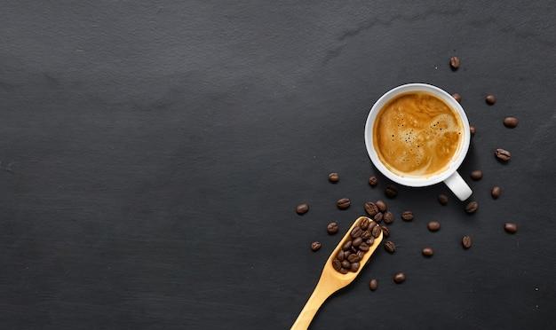 Горячий эспрессо и кофейные зерна на фоне черного деревянного стола. вид сверху