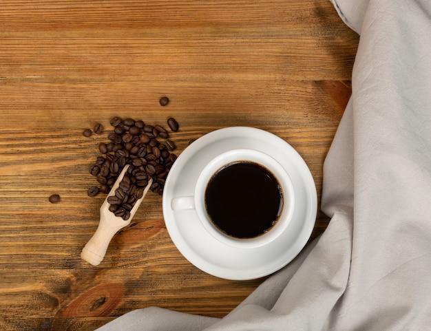 ホットのエスプレッソカップと茶色の木製のテーブルバックグラウンドトップビューでコーヒー豆。