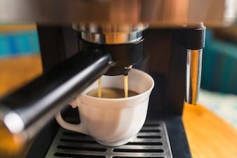 Hot espresso pouring into porcelain mug