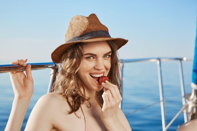 Hot european model eating strawberry while sitting on yacht under sun, wearing straw hat.