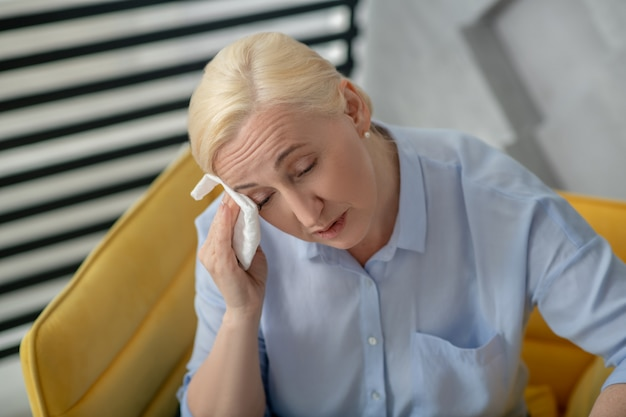 Hot, feeling unwell. woman blonde with closed eyes wiping her face with a napkin frowning forehead unhappy.